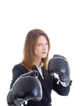 Caucasian businesswoman in a suit wearing boxing gloves, ready for a fight.  Shes glaring at the camera.  Isolated on white background. photo