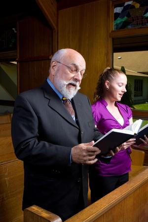 hymnal: Young woman senior man singing in church.