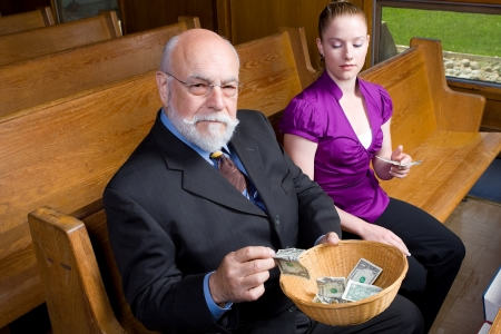 Senior man and young woman putting money into a church offering basket.  Looking at camera while sitting in Pew.