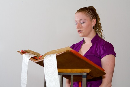 reciting: Young woman reading out loud from large bible on a church lectern.