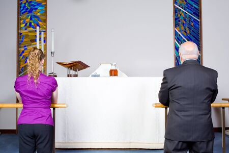 Rear view of two people taking communion in a church.