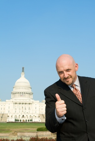 Happy white man giving a thumbs up gesture in front of the U.S. Capitol building in Washington, DC. photo