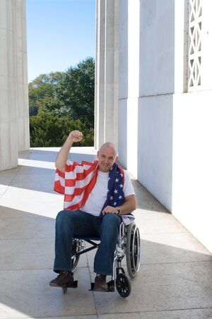 Patriotic white man sitting in a wheelchair with raised fist and American flag draped across his shoulders.
