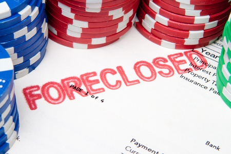 foreclosed: Mortgage document with foreclosed stamped on it, surrounded by poker chips.  Suggesting the current US mortgage crisis. Stock Photo
