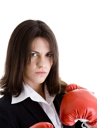 glaring: Angry woman in a suit with boxing gloves isolated on white.