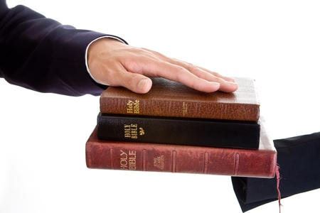 Mans hand on a stack of bibles.  Swearing on a stack of bible theme.  Isolated on white background photo