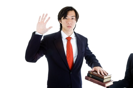 Asian man swearing on a stack of bibles Stock Photo