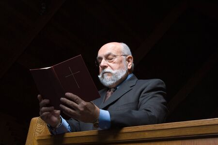 hymnal: Senior Caucasian man kneeling against church pew, reading from hymnal.  Church is dark Isolated on black