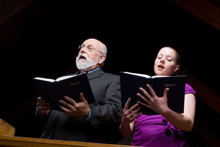 Older man and young woman singing in a pew with hymnals. photo