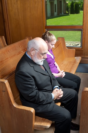 bowing head: Senior and young woman praying in church pew. Stock Photo