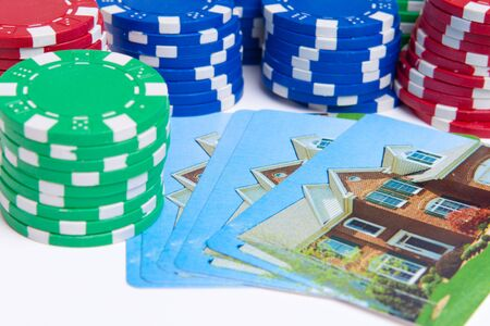 Playing cards with house printed on them next to stacks of poker chips.  Gambling on real estate theme. photo