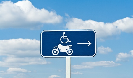 se�al parking: Discapacitados y el signo de motocicletas de estacionamiento, contra un cielo azul
