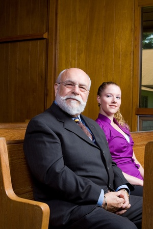 bald girl: Older Caucasian man and young woman sitting in church pew, smiling at camera.