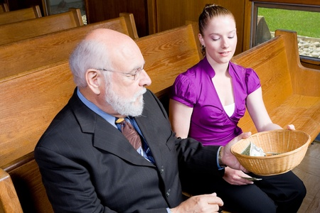 pew: Grandfather passing offering basket to granddaughter in church pew.