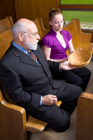 pew: Older man and young woman sitting on a pew in church looking at an empty offering basket.