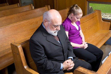 head down: Senior white man and young woman praying in church.