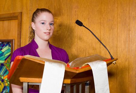 Woman standing at pulpit reading from large bible. Zdjęcie Seryjne