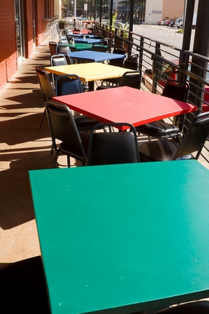 saturated color: Square tables in primary colors on restaurant balcony.