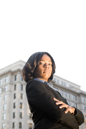 Tough-Looking African American businesswoman with serious expression looking at camera.  Shot outdoors with office building and blown out sky.