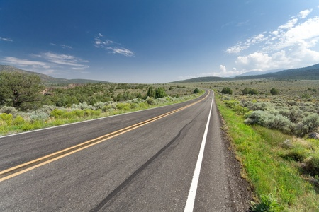Wide angle shot of a highway outside Taos, New Mexico.  Skid mark in the foreground.