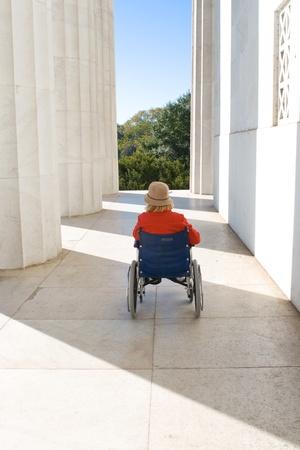 paraplegico: Mujer en silla de ruedas fuera del Monumento a Lincoln. De espaldas, mirando hacia el espacio entre las columnas y la construcción. Foto de archivo