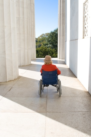 paraplegic: Woman in a wheelchair outside the Lincoln Memorial.  Facing away, looking toward space between columns and building. Stock Photo