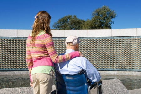 Grandfather in wheelchair granddaughter looking at the stars in the World War II Memorial in Washington, DC.  Each star represents 100 Americans killed during the war. photo