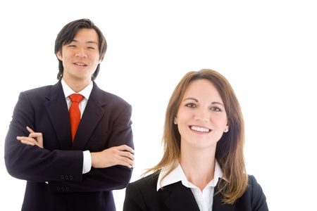 Caucasian business woman in foreground and Asian business man in background.  Both are wearing suits.  Isolated on white background. photo
