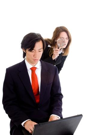 Jonge blanke vrouw peering over de schouder van een Aziatische zakenman met een vergrootglas. Industriële spionage thema