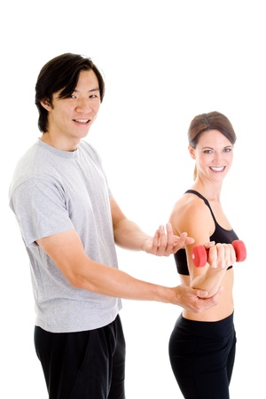 Asian man helping Caucasian woman with her form while she works out.  Isolated on white background. photo