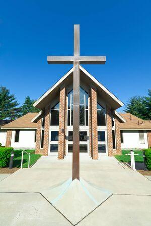 gabled: Front view of A-frame church and cross.  Shot with wide angle lens. Stock Photo