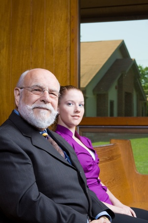pew: Senior man and young woman sitting in a church pew.  Looking at Camera.