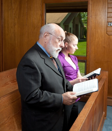 Older man and younger woman standing and singing in a church. photo
