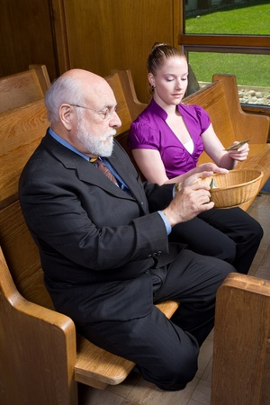 pew: Older man and young woman putting money into an offering basket.  Sitting in a church pew. Stock Photo