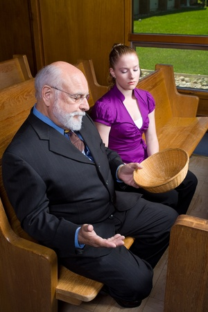 pew: Senior man and young woman looking at an empty offering basket.  Sitting in a church pew. Stock Photo