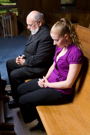 Senior man and young woman praying in church.  Sitting in a Pew. photo
