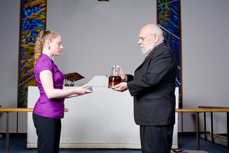 layman: Senior man and young woman, church laypeople, holding the components of holy communion in front of the alter, in a church.