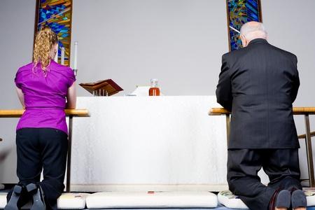 mujer arrodillada: Hombre mayor y mujer joven arrodillada en el comulgatorio en una iglesia Foto de archivo