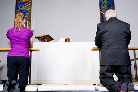 kneeling man: Senior man and young woman kneeling at the communion rail in a church