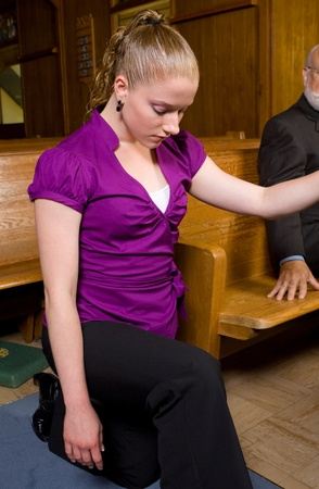 causasian: Young causasian woman kneeling in church aisle.