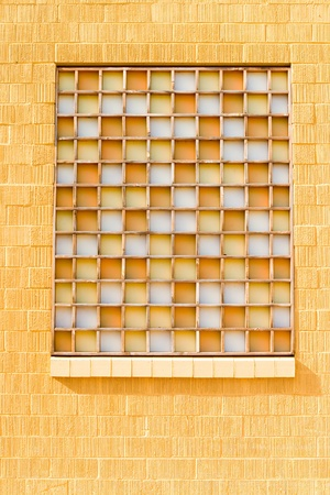 lattice window: A yellow window in a yellow wall Stock Photo