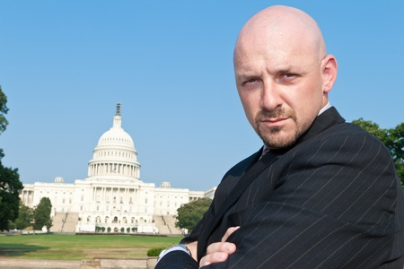 Bald man with serious expression and crossed arms looking at the camera with U.S. Capitol Building in the background, Washington, DC.  He looks like a beltway power broker.