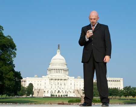 federal states: Businessman checking a smart phone in front of the U.S. Capital building in Washington, DC, United States.