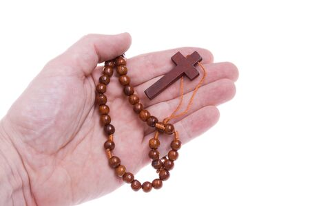 Hand holding a rosary on a white background. photo