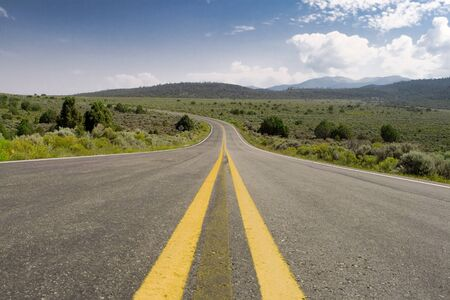 single lane road: Middle of the road in north central New Mexico, USA., Sangre de Cristo Mountains off in the distance.