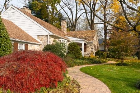 Bochtige stoep en het huis in een buitenwijk van Philadelphia, Pennsylvania, Verenigde Staten in de herfst. Japanse esdoorn in de linker voorgrond.