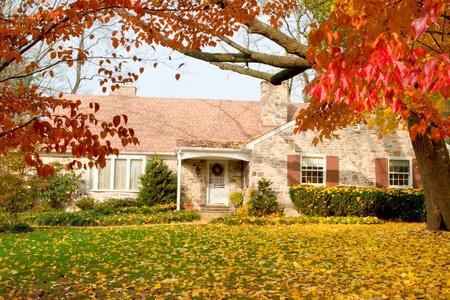 Eengezinswoning met herfstbladeren. Dogwood bomen op de voorgrond, de gele bladeren zijn Noorse esdoorn. Suburban Philadelphia, PA, Verenigde Staten.