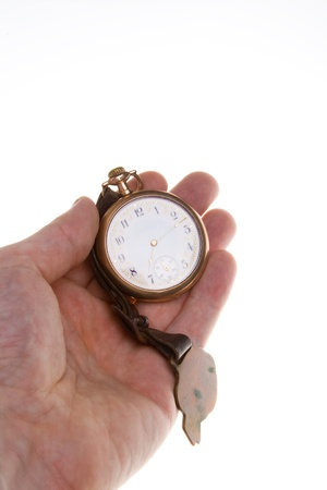 Hand holding brass pocket watch with leather strap.