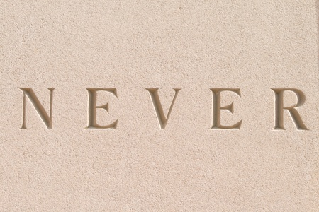 never: The word never carved in sandstone