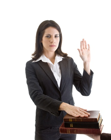 an oath: White woman with raised hand, swearing on a stack of bibles in a suit.  Isolated on white background. Stock Photo